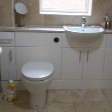 toilet and sink with custom fitted bathroom storage